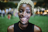 Portrait of smiling young woman in a park at night - GIOF01466