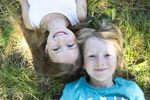 Portrait of brother and little sister lying on a meadow looking up to camera - SARF02903