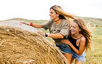Two best friends climbing on straw bale - MGOF02434