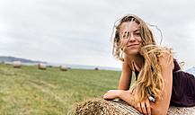 Portrait of smiling blond teenage girl with blowing hair lying on straw bale - MGOF02437