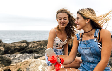 Two best friends listening music together with earphones at the coast - MGOF02455