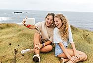 Two screaming teenage girls taking selfie at the coast - MGOF02464