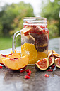 Glass of infused water with orange slices, fig, pomegranate seed, nectarine and plums - SARF02907