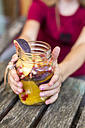 Hands of a girl holding glass of infused water with various fruits - SARF02910
