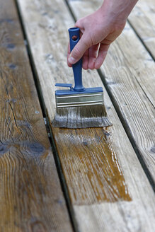 Hand applying glaze on planks, close-up - LBF01468