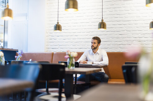 Businessman sitting in a cafe with cup of coffee - DIGF01240