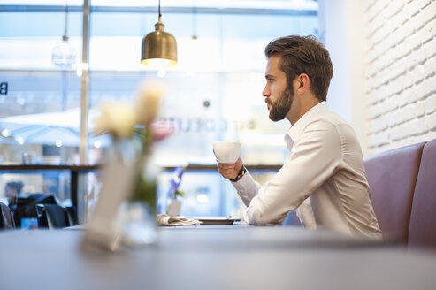 Businessman sitting in a cafe with cup of coffee - DIGF01243