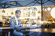 Businessman using laptop in a cafe - DIGF01255