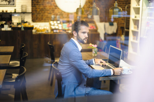 Businessman with laptop in a cafe - DIGF01258