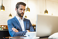 Businessman looking at laptop in a cafe - DIGF01261