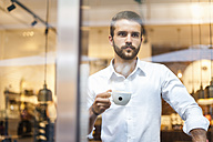 Businessman holding cup of coffee looking through window - DIGF01267