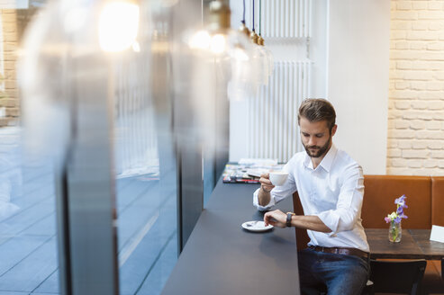 Businessman in a cafe checking the time - DIGF01273