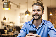 Smiling young man with cell phone in a cafe - DIGF01282