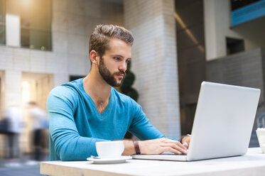 Young man sitting at table using laptop - DIGF01294
