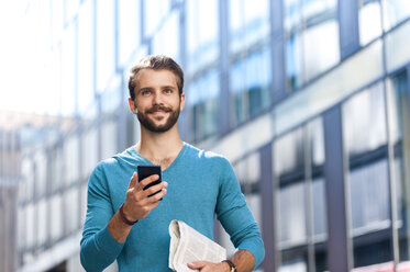 Smiling young man holding cell phone and newspaper in the city - DIGF01306