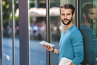 Young man holding tablet and newspaper at glass front of a building - DIGF01309