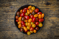 Bowl of yellow and red mini tomatoes on wood - LVF05330