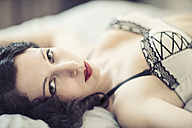 Young woman in lingerie lying on bed - TAMF00653