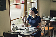 Young woman in a cafe looking out of window - TAMF00659