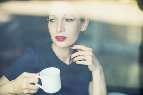 Young woman in a cafe looking out of window - TAMF00662