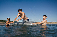 Three playful friends with airbed in the sea - DAPF00356