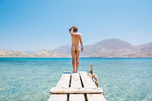 Greece, Cyclades islands, Amorgos, Aegean Sea, naked man standing on the edge of a wooden jetty - GEMF01022
