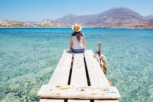 Greece, Cyclades islands, Amorgos, woman sitting on the edge of a wooden pier, Nikouria island - GEMF01025