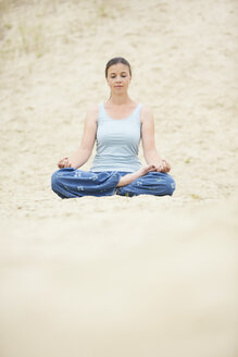 Woman with closed eyes relaxing in Lotus position in sand - MAEF12027