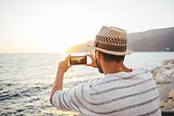 Greece, Cylcades Islands, Amorgos, man taking pictures of the sunset with a smartphone next to the sea - GEMF01032