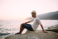 Greece, Cylcades Islands, Amorgos, man enjoying the sunset next to the sea - GEMF01041