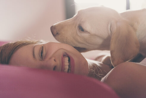 Happy young woman lying on bed playing with her Labrador Retriever puppy - SKCF00203