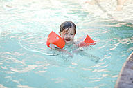 Little girl with floating tire in swimming pool - SHKF00673