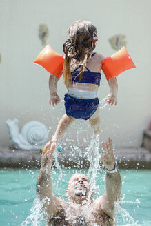 Father playing with little daughter in swimming pool - SHKF00682