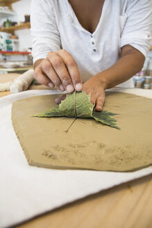 Woman using a leaf to print a draw in terracota in a ceramics workshop - ABZF01245