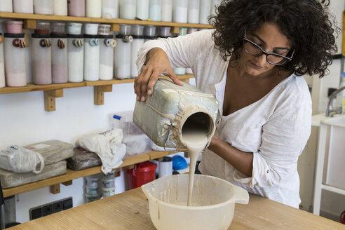 Woman pouring liquid porcelain into a bowl - ABZF01257