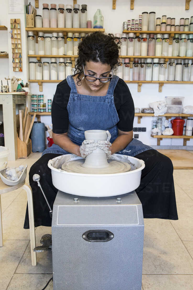 Woman working with a pottery wheel in her workshop - ABZF01272 - Andrés Benitez/Westend61