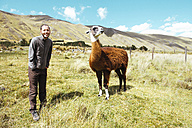 Peru, Huaraz, traveler with a llama in a meadow - GEMF01054
