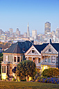 USA, California, San Francisco, Victorian houses on Steiner Street at Alamo Square in front of the skyline - BRF01399