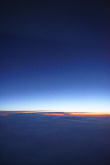 USA, view out of plane window on sunset above the clouds - BRF01411