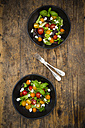 Two bowls of leaf salad with goat cream cheese and tomatoes on wood - LVF05338