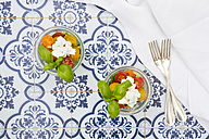 Teo glasses of leaf salad with goat cream cheese and tomatoes on tiles - LVF05344