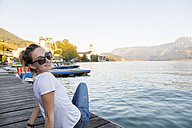 Austria, Sankt Wolfgang, smiling woman sitting on jetty at lake - JUNF00627
