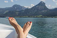 Austria, Sankt Wolfgang, woman's feet on boat in lake - JUNF00633
