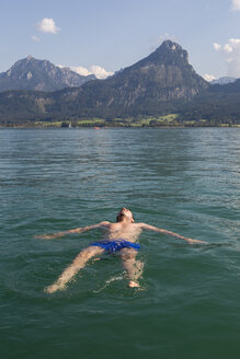 Austria, Sankt Wolfgang, man floating in lake - JUNF00636