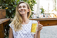 Happy woman with beer mug in a street restaurant looking up - JUNF00651