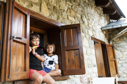 Two little brothers relaxing on window sill of holiday home - VABF00776