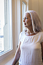 Mature woman looking through window - JUNF00663