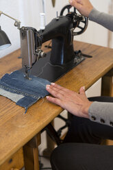 Woman working at sewing machine at home, partial view - JUNF00684