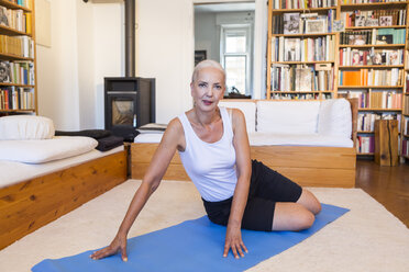 Portrait of woman sitting on gym mat in living room - JUNF00696