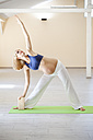 Prenatal yoga, woman doing triangle pose - ZEDF00328